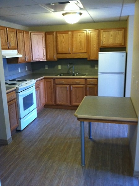 Margaret Wagner Apartments kitchen with light wood cabinets, white appliances, and small table
