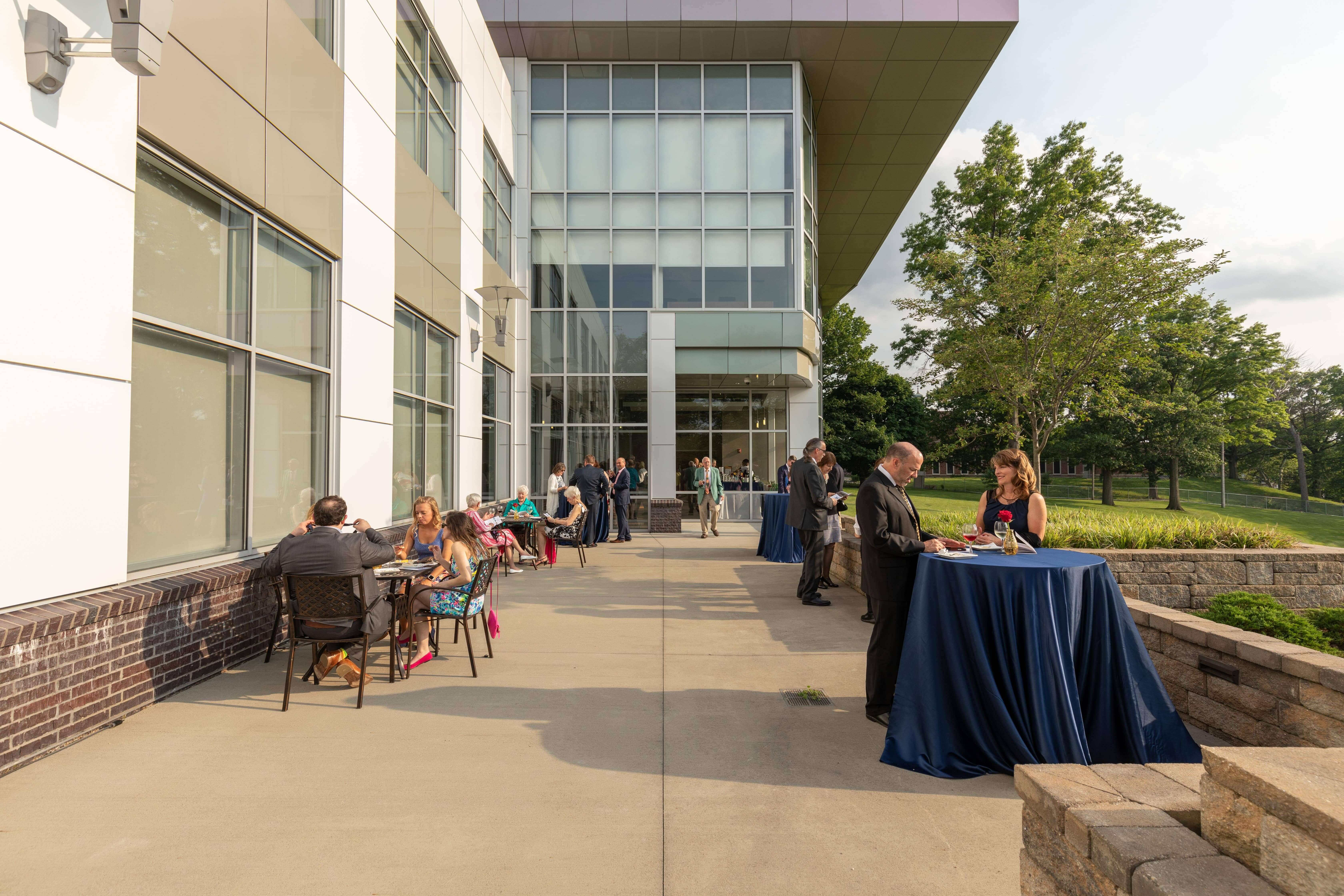 Event attendees eating and talking outside on the Conference Center at Benjamin Rose patio
